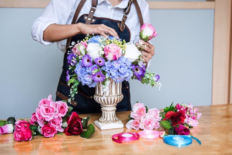 Vereinbarend bekleiden k?nstliche Blumen Dekoration zu Hause, die Floristenarbeit der jungen Frau, die organisierende diy k?nstli stockbild