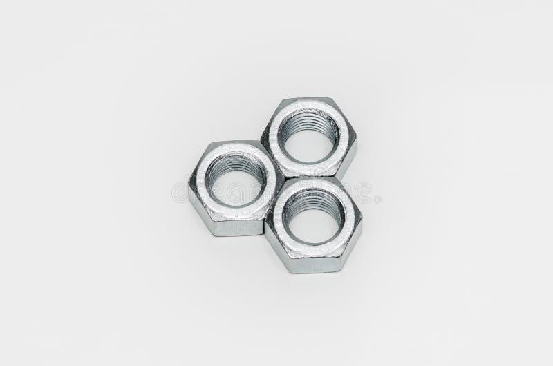 Vereinbarte Metallnüsse auf weißem Hintergrund stockfotografie