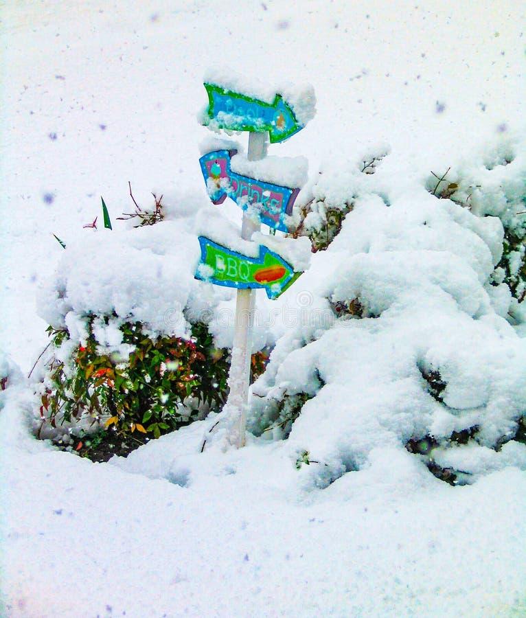 Vereinigen Sie barbque und Getränkminiwegweiser, der im Schnee mit mehr Schnee umfasst wird, der unten kommt lizenzfreie stockfotografie