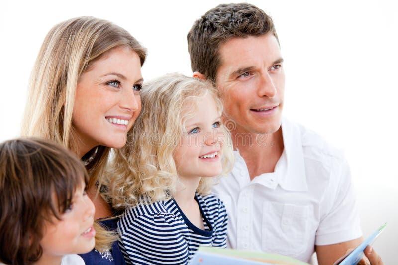 Vereinigte Familie, die ein Buch liest lizenzfreie stockfotos