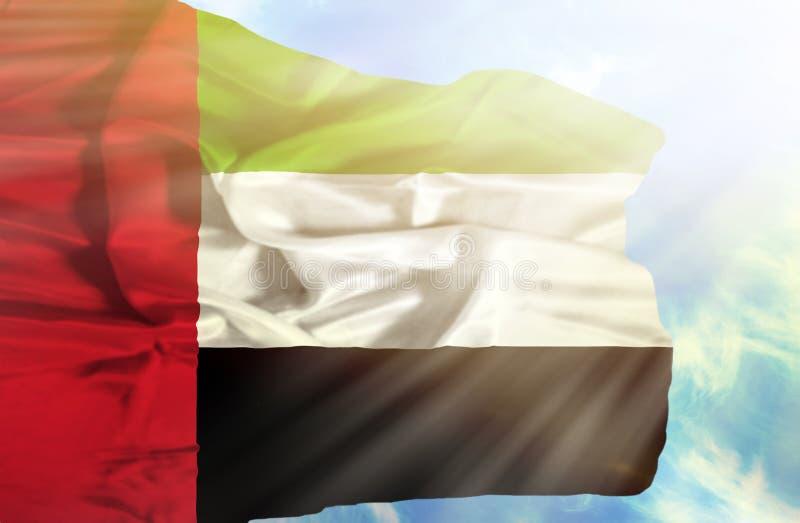 Verenigde Arabische Emiraten die vlag golven tegen blauwe hemel met zonnestralen royalty-vrije stock afbeeldingen