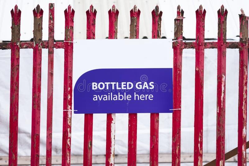 Verfügbares hier Zeichen des Flaschengases auf rotem mit der Eisenbahn beförderndem Zaun lizenzfreies stockbild