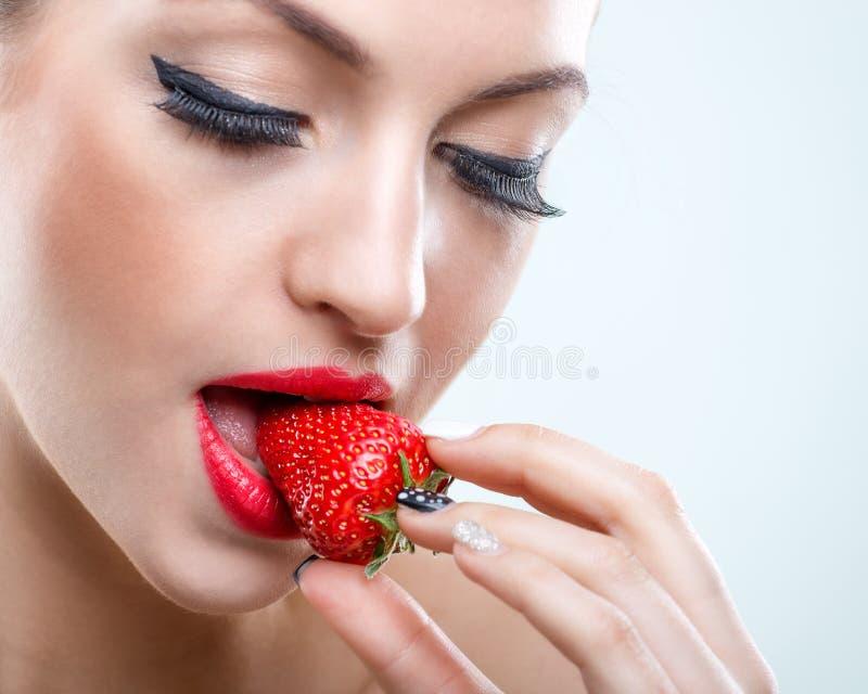 Verführung - Schönheit, wenn geschlossene Augen, einen Biss der Erdbeere nehmen stockbild