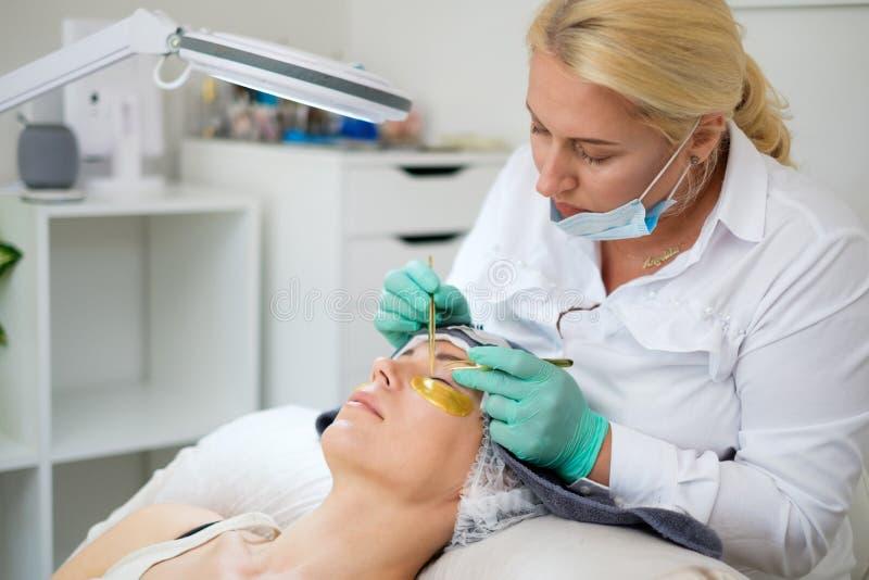 Verfahren der Wimpererweiterung im Salon durch Kosmetiker stockfotografie