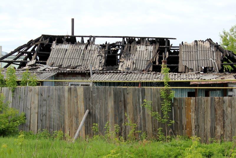 Verfallenes ländliches Haus nach den Feuerständen hinter dem Zaun stockfoto