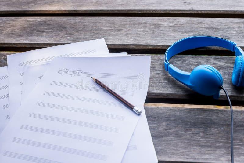 verfassende Musik mit blauem Kopfhörer und auf dem hölzernen Schreibtisch lizenzfreies stockbild