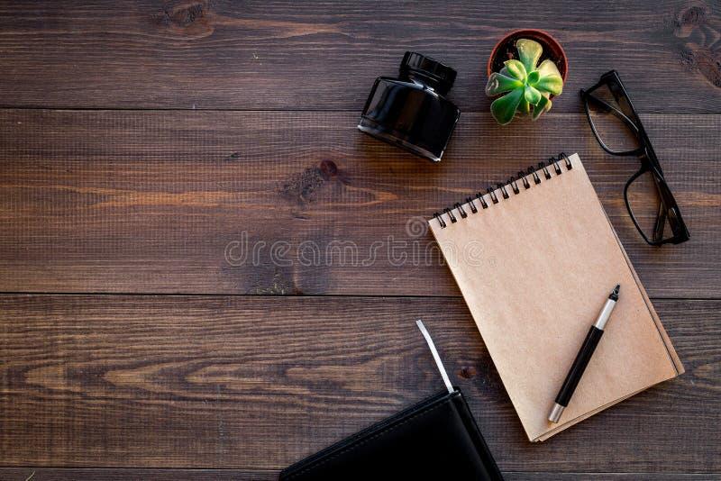 Verfasserberuf Retro- Konzept Notizbuch, Stift, Inkpot, Gläser auf dunklem hölzernem Draufsicht-Kopienraum des Hintergrundes stockfoto