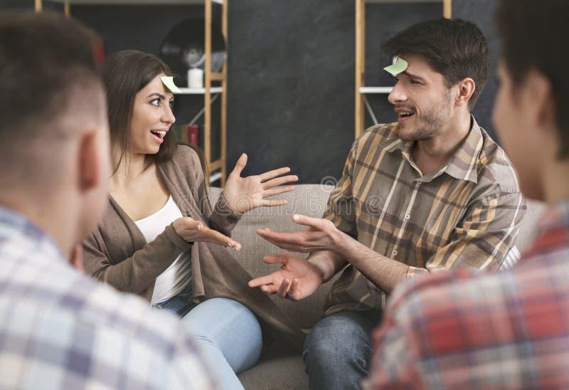 Verfasste Paare, die Stirndetektivspiel mit Freunden spielen lizenzfreie stockfotos