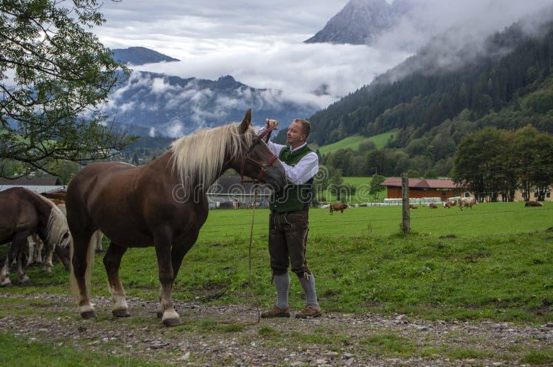 Verfenveng, Salsburg/Austria - 23 settembre 2018: Il giovane in costume austriaco verde tradizionale lancia il cavallo sul pascol fotografia stock