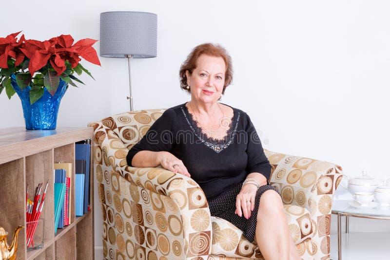 Verfijnde hogere vrouw die thuis ontspannen stock foto