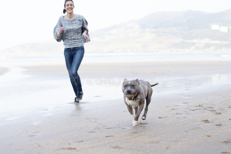 Verfolgen Sie Betrieb und das Spielen mit Ball im Strand. lizenzfreie stockfotos