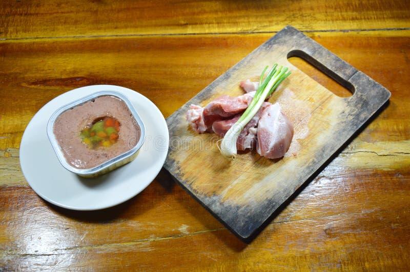 Verfolgen Sie erstklassiges Nassfutter im Behälter und im frischen rohen Schweinefleisch auf Hiebblock lizenzfreies stockfoto