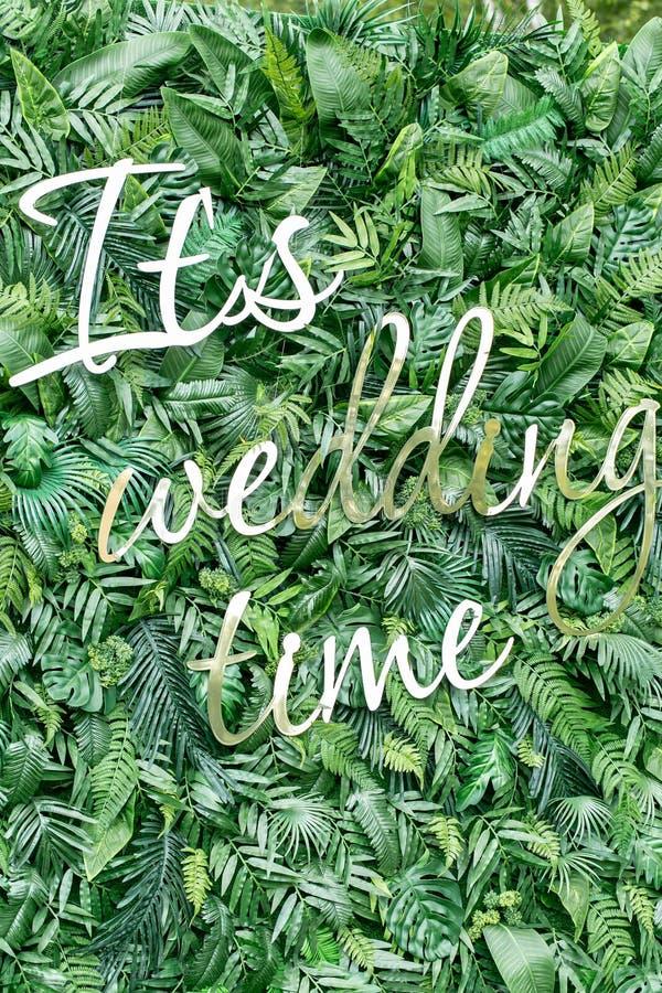 Verfraai muurachtergrond van kunstmatig blad en glanzende brieven Het is huwelijkstijd royalty-vrije stock foto
