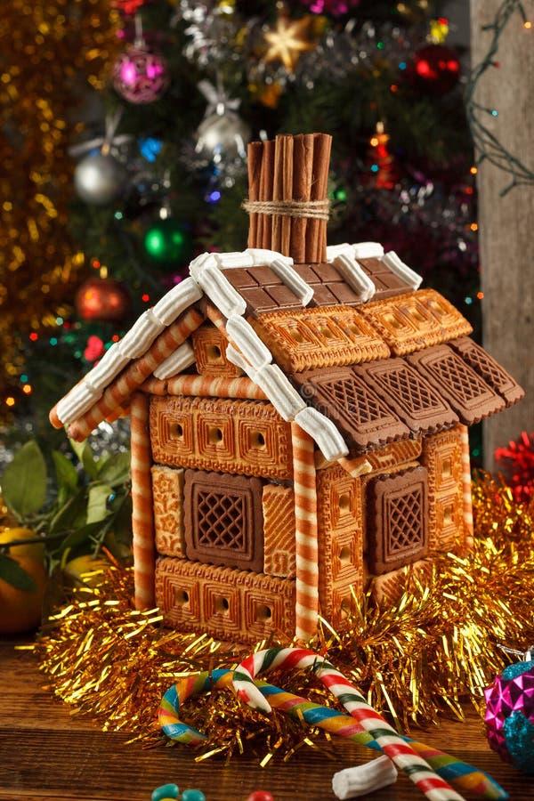 Verfraaid peperkoekhuis en Kerstmissnoepjes op de achtergrond van een geklede Kerstboom stock afbeelding