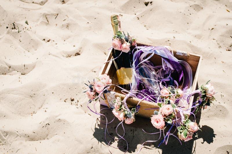 Verfraaide doos met champagne, wijn en glas op het strand stock afbeeldingen