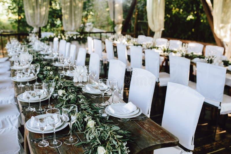 Verfraaide elegante houten huwelijkslijst voor banket openlucht in tuin, in de stijl van plattelander met eucalyptus en bloemen,  royalty-vrije stock afbeelding