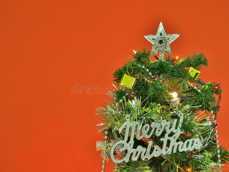 Verfraaide Kerstboom met Vrolijk Kerstmisteken op rode muurachtergrond stock afbeeldingen