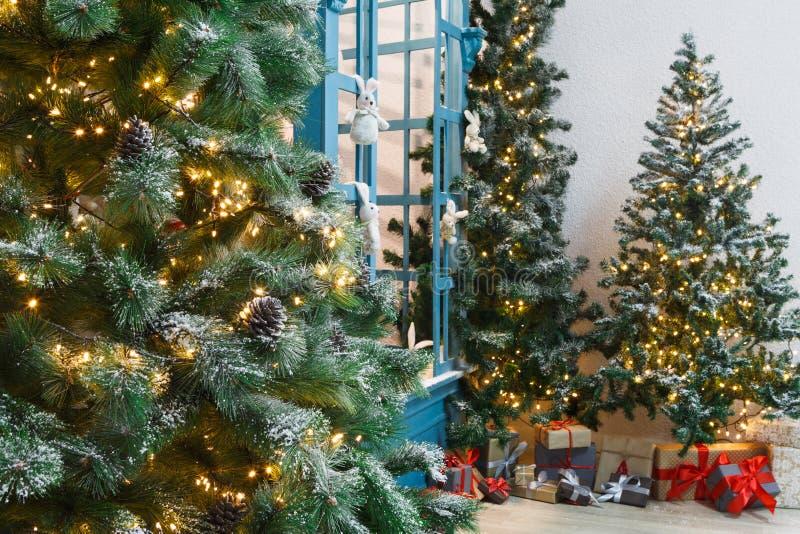 Verfraaide Kerstmisbomen op glanzende slingerachtergrond stock foto