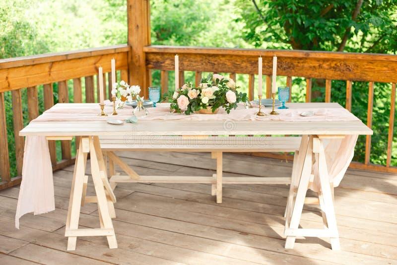 Verfraaide lijst voor diner voor tweepersoons, met platenmes, vork, kaas, wijn, wijnglazen en bloemen in een koper stock fotografie