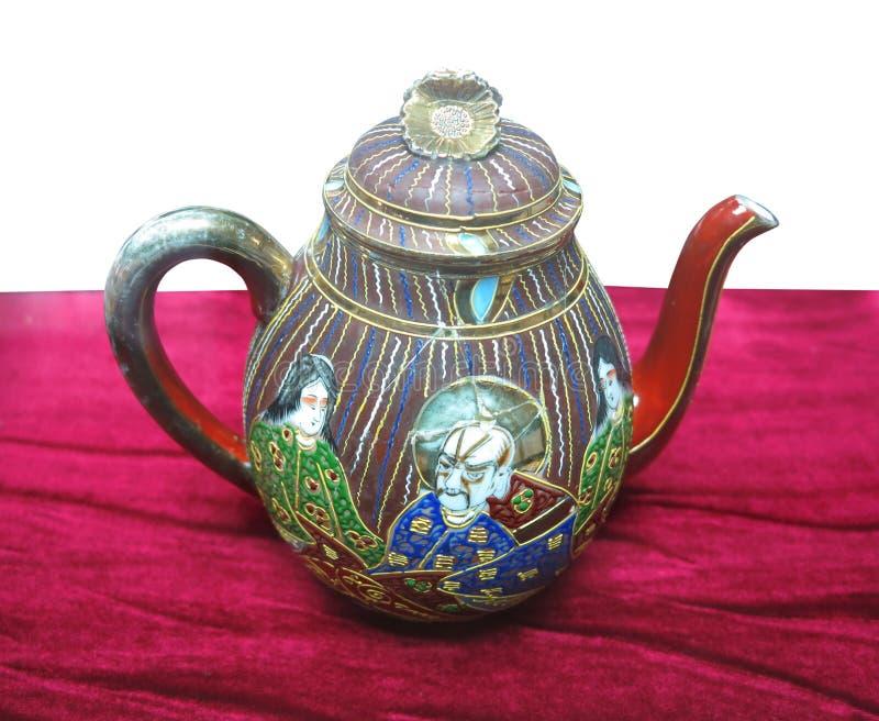 Verfraaide oude kleurrijke Chinese ceramische theepot op rood royalty-vrije stock afbeelding