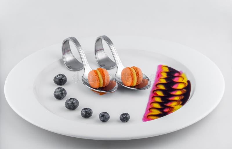 Verfraaide plaatsinaasappel macrons met framboos stock fotografie