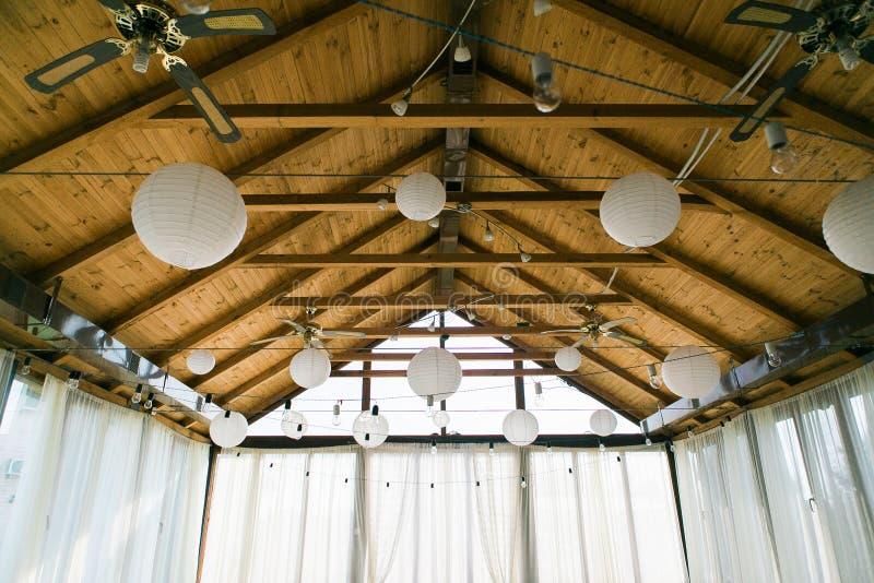 Verfraaide tent met bolslinger Het Witboeklantaarns van de huwelijksopstelling binnen van de bouw, onder houten dakdecoratie royalty-vrije stock afbeeldingen