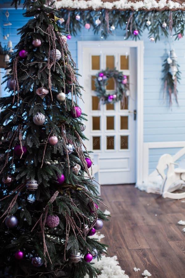 Verfraaide vakantieboom bij de achtergrond van een witte deur stock foto