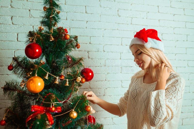 Verfraait het pret jonge blonde een Kerstmisboom in santahoed royalty-vrije stock afbeelding