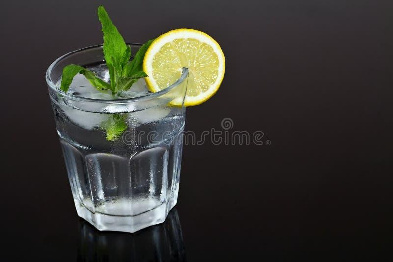 Verfrissend die glas water met ijsblokjes met citroen en munt op smaak worden gebracht De zomerverfrissing royalty-vrije stock afbeelding