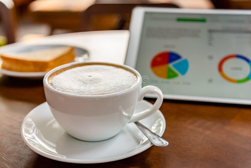 Verfrissend en heerlijk bedrijfsontbijt met koffie latte, tonijnsandwich en tablet voor het werk stock fotografie