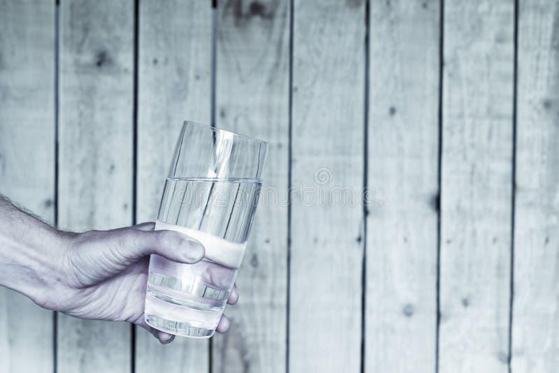 Verfrissend glas koud water die door mannelijke hand worden aangeboden die een glas houden royalty-vrije stock fotografie