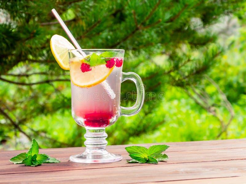 Verfrissende de zomercocktail met citroen, framboos en munt een houten lijst royalty-vrije stock foto's