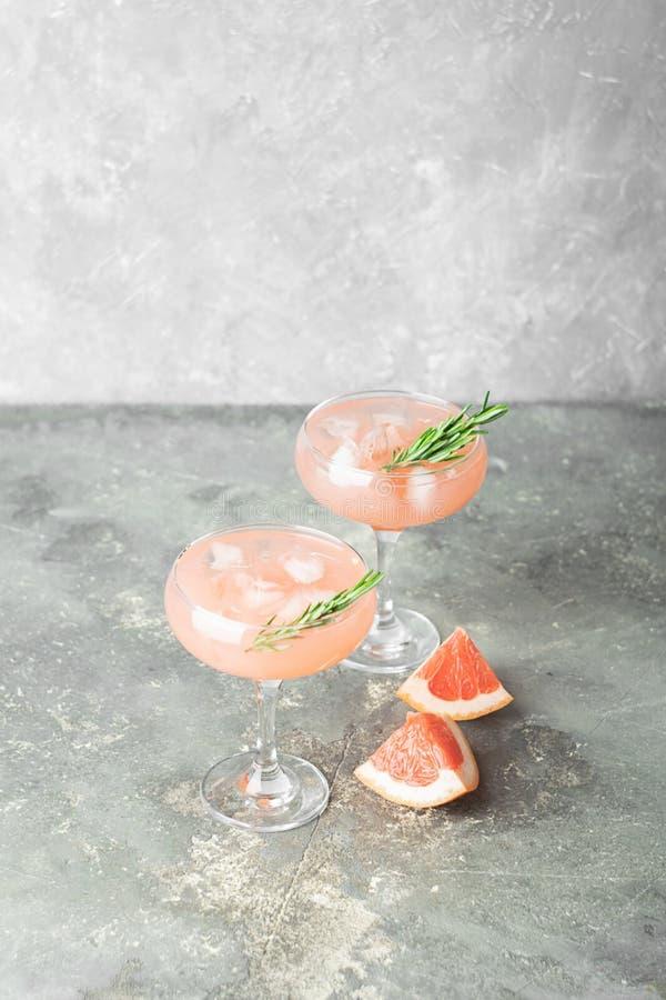 Verfrissende de zomercocktail van grapefruit juice van rozemarijn en ijs in twee glasglazen op grijze achtergrond van beton stock foto