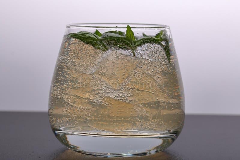 Verfrissende drank met gasbellen Nalit in een transparant glas Het legde verpletterd ijs Verfraaid met muntbladeren stock foto