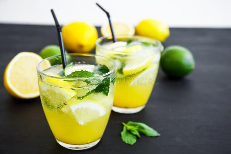 Verfrissende limonade in glas met kalk, citroenen en munt De zomerdranken stock foto