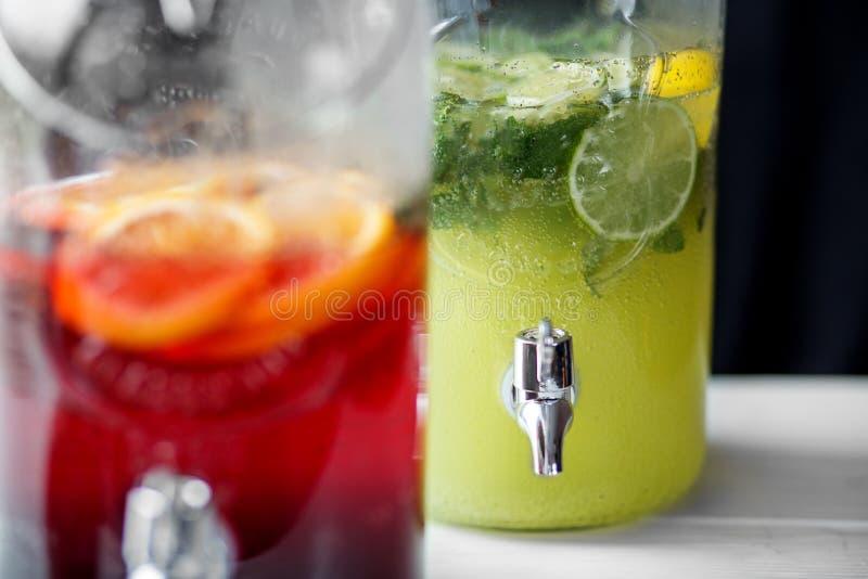 Verfrissende limonade met kalk, munt, sinaasappel en granaatappel in glaskruiken met tapkraan Concept dranken, de zomer, bar, rus stock foto