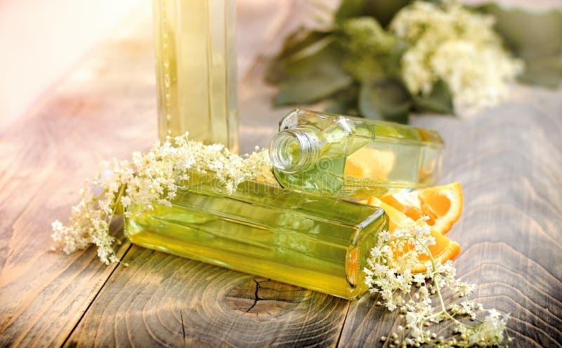 Verfrissing gezond sap van vlierbesbloemen en sinaasappel op rustieke lijst stock foto