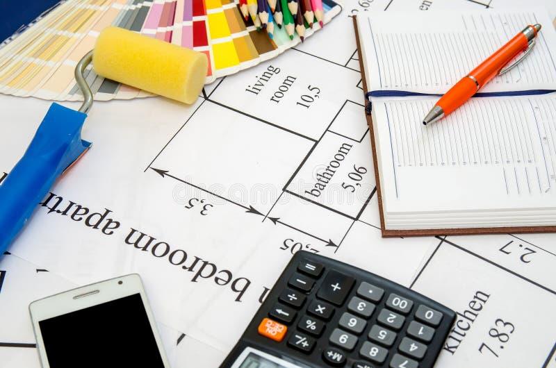 Verfrol, potlood, notitieboekje en kleurengids op architecturale tekeningen royalty-vrije stock afbeelding