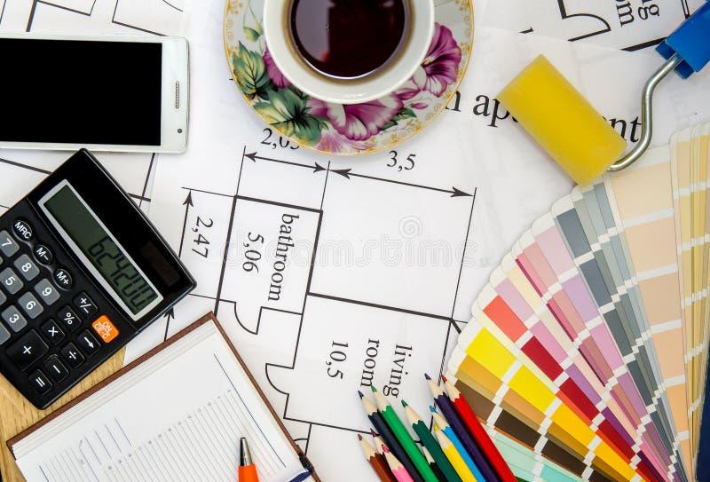 Verfrol, potlood, notitieboekje en kleurengids op architecturale tekeningen royalty-vrije stock fotografie