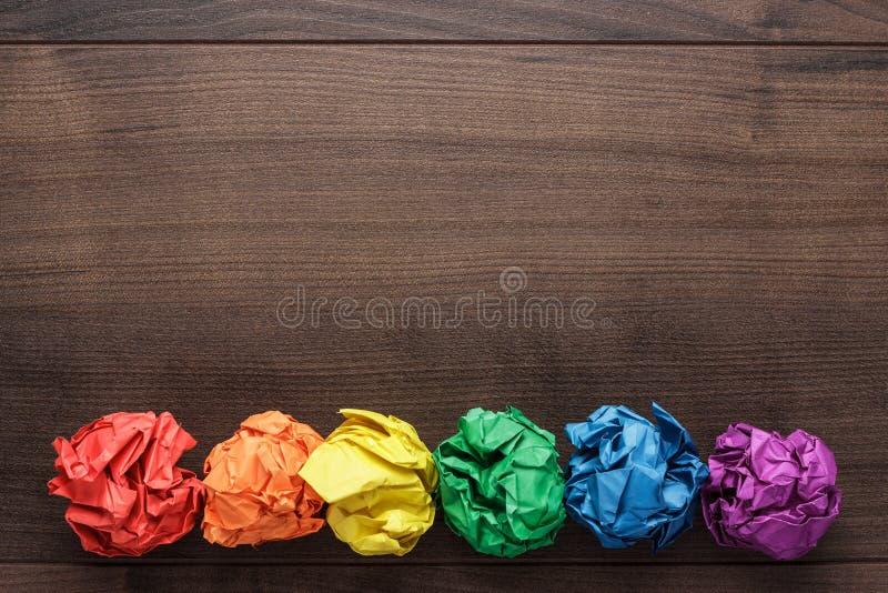Verfrommeld kleurrijk document op houten achtergrond stock foto's