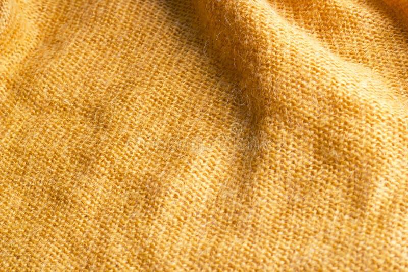 Verfrommelde gele gebreide textiel met gevouwen voor achtergrond stock afbeelding
