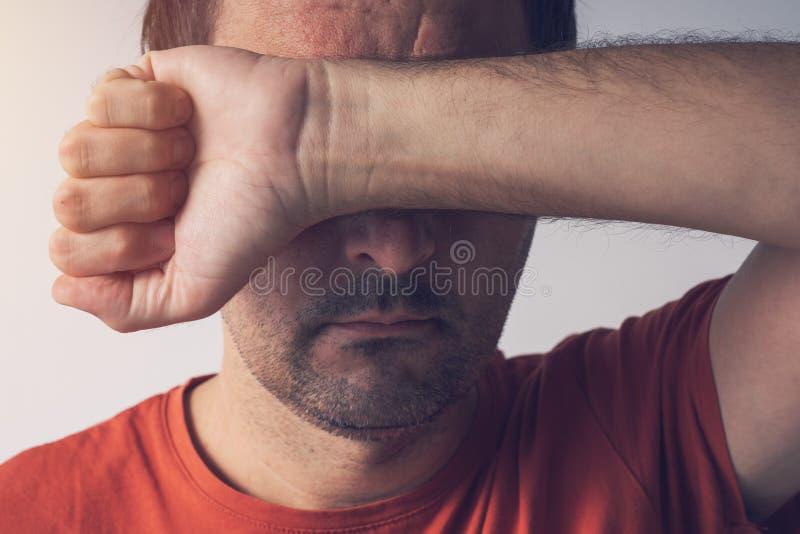 Vergüenza y culpabilidad, cara de la cubierta del hombre foto de archivo libre de regalías