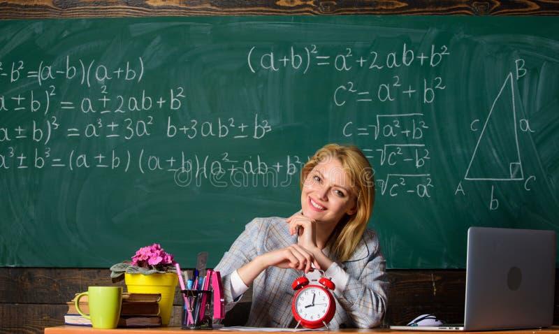 Verg uw tijd leraar met wekker bij bord Tijd Studie en onderwijs Moderne School De Dag van de kennis school stock afbeelding