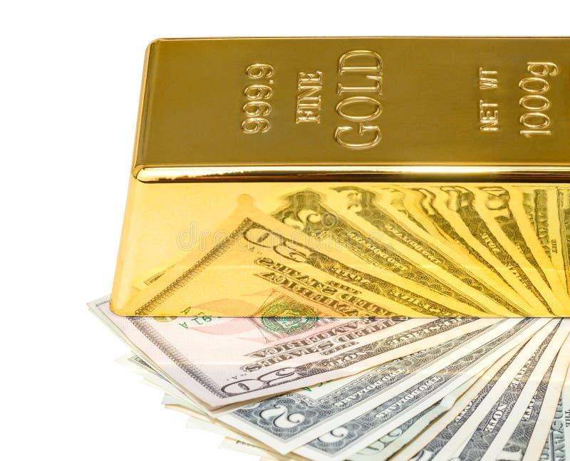 Verga d'oro e banconote in dollari fotografie stock libere da diritti