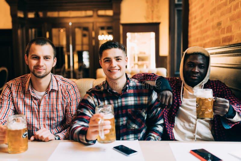 Vergadering met de beste vrienden Drie gelukkige jonge mensen in vrijetijdskleding die en het drinken bier terwijl samen het zitt royalty-vrije stock afbeelding