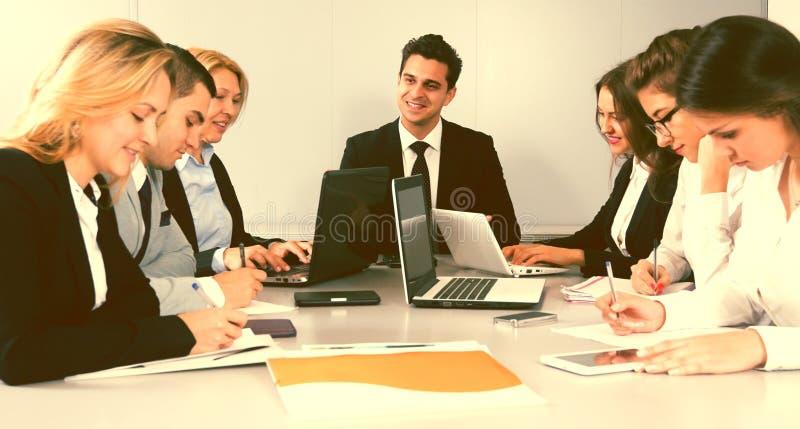 Vergadering van bedienden in conferentieruimte stock afbeelding