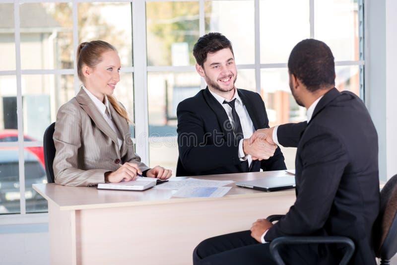 Vergadering van partners Drie succesvolle bedrijfsmensen die aanwezig zijn stock afbeelding