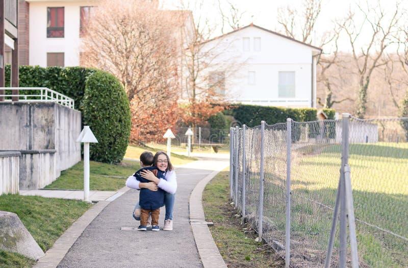 Vergadering van zuster en broer Gelukkig tween meisje die haar koesteren weinig broer gelukkig om hem te zien stock afbeelding
