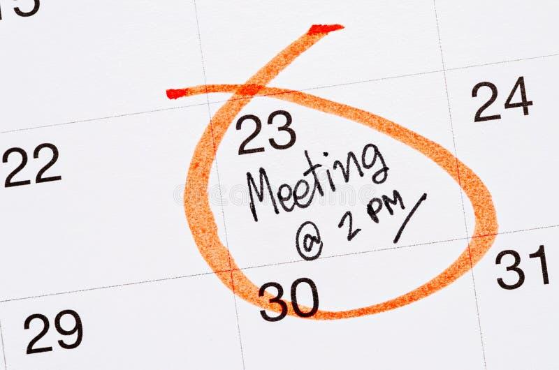 Vergaderingsbenoeming die in een kalender wordt geschreven stock afbeeldingen