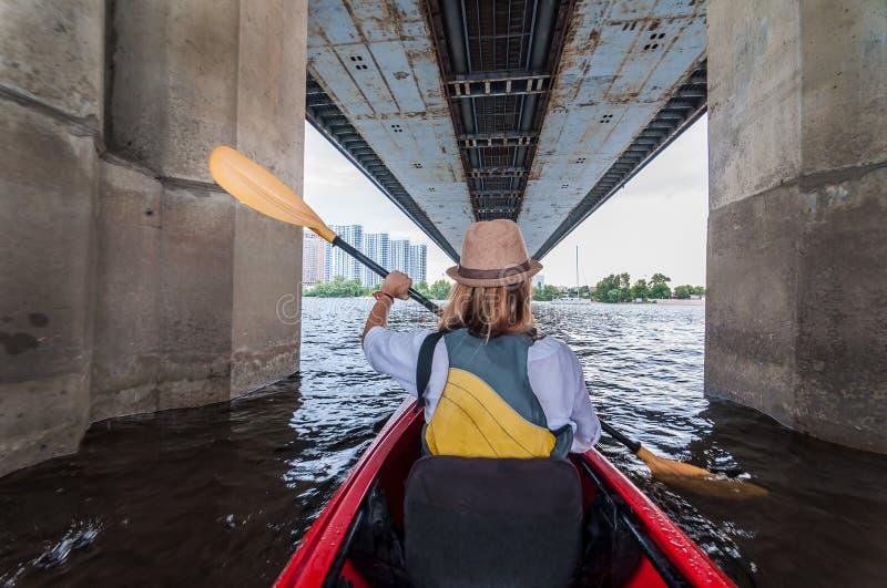 Vergaderingsochtend op kajaks Achtermening van jonge meisjes kayaking bu de rivier en onder de brug Stedelijk exploratieconcept stock fotografie